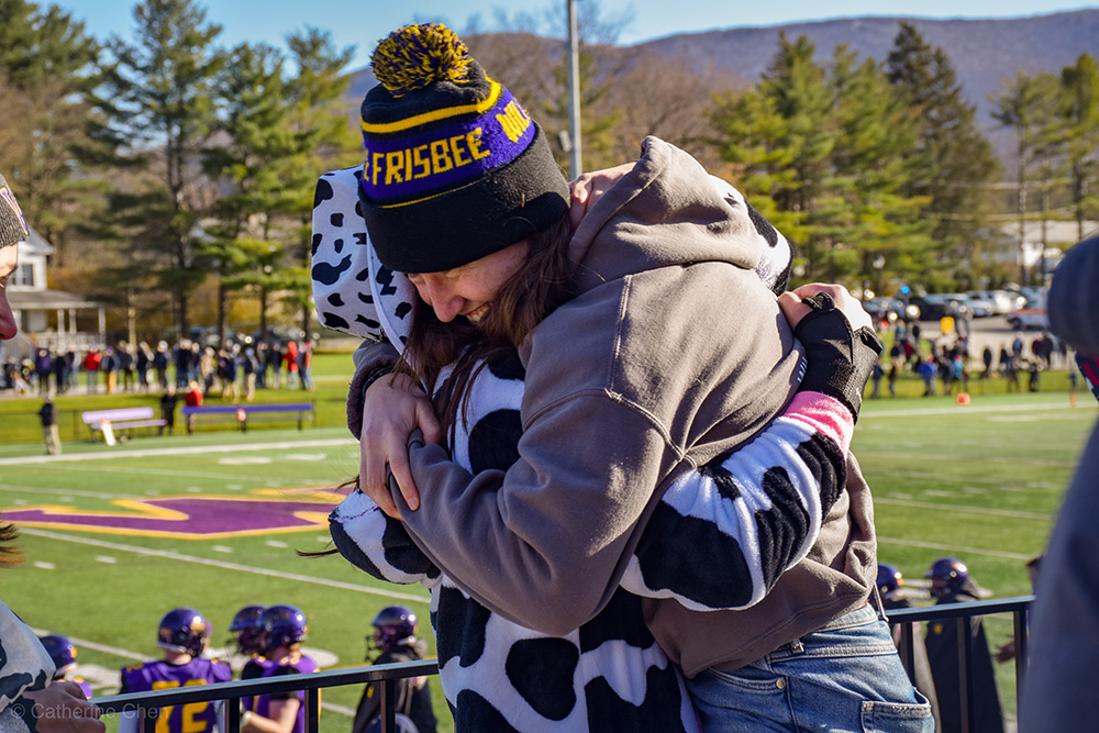 students hugging after football win over Amherst
