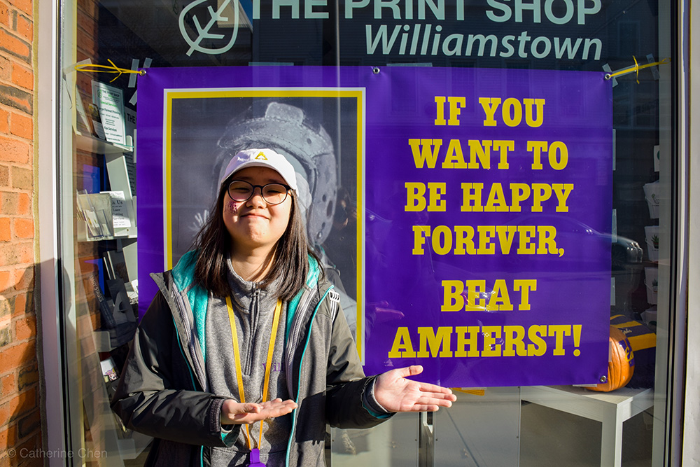 """student next to """"beat Amherst"""" sign"""