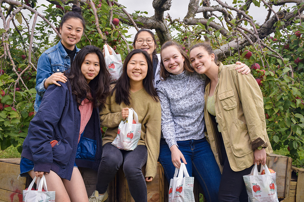 students posing by apple tree