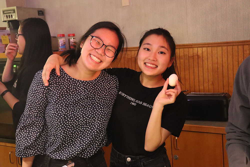 two students joking with boiled egg