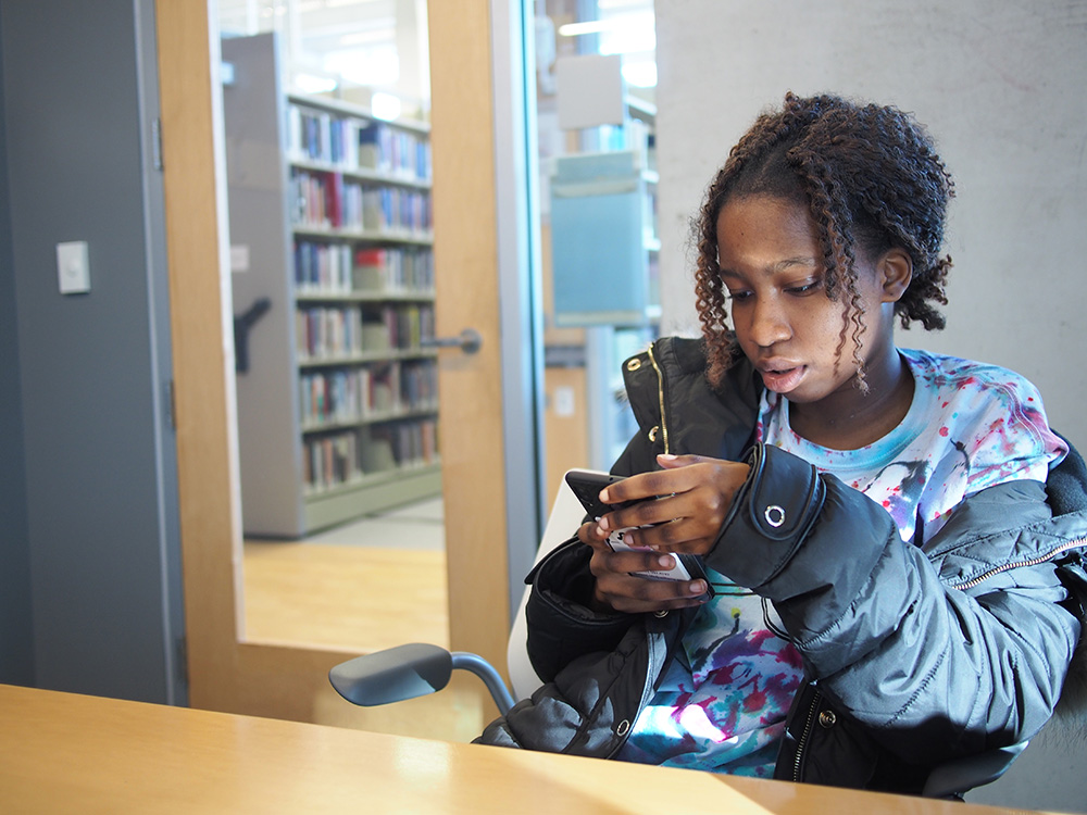 student looking at cell phone in library