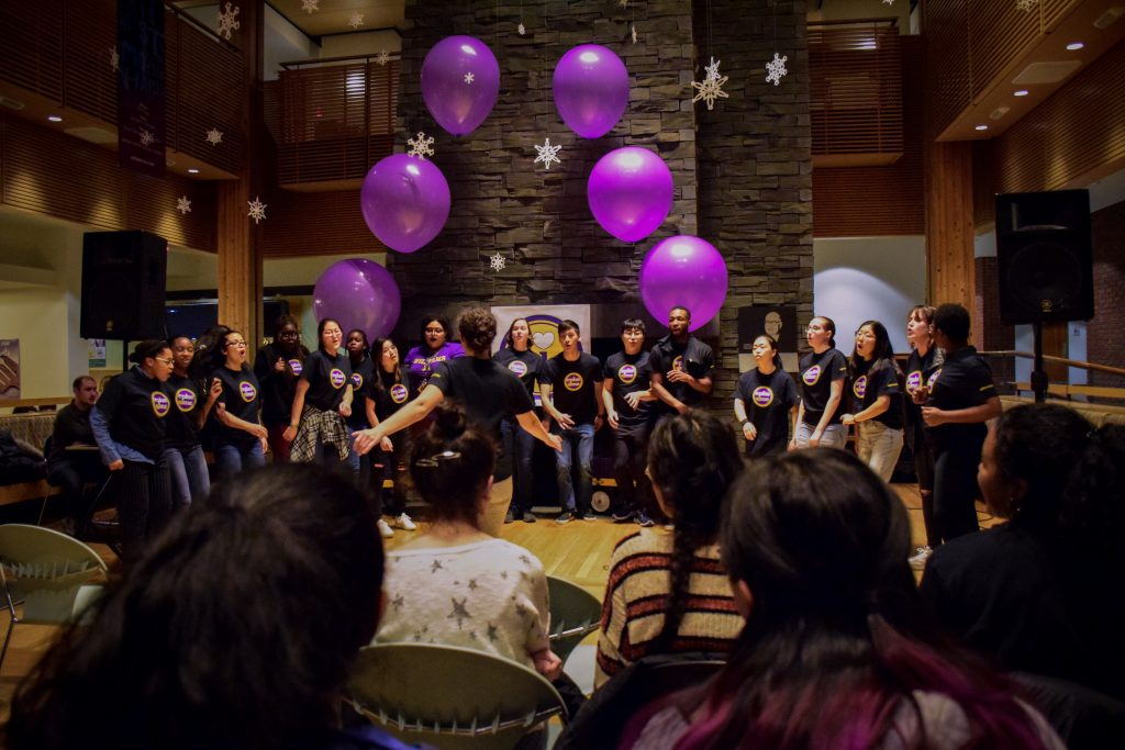 Students singing in Paresky with purple balloons